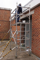 A painter working from a scaffold tower
