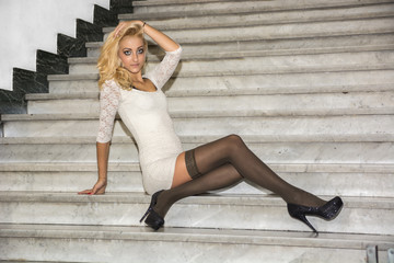 Elegant pretty blonde young woman sitting on marble stairs