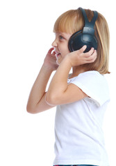 girl listening to music with big black headphones standing sidew