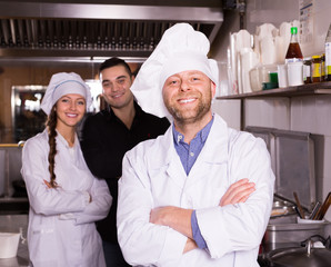 Portrait of chef with helpers