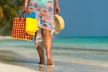 Woman  on a tropical beach with orange bag