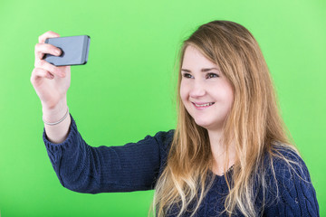 Young Woman Taking a Selfie on Green Background.