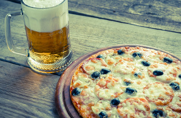 Cooked pizza with a glass of beer