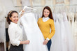 Woman helps the bride in choosing bridal gown
