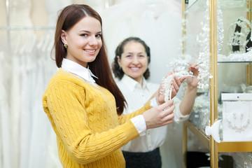 woman helps the bride in choosing bridal accessories