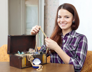 girl looks jewelry in treasure chest