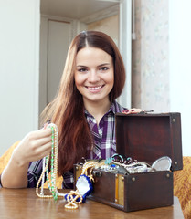 woman chooses jewelry in treasure chest