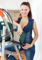 beautiful  girl in overalls with drill