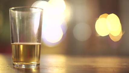 Nearly finished glass of beer with blurred background lights