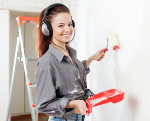 Happy  woman in headphones paints wal
