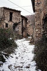 sentiero innevato fra vecchi ruderi