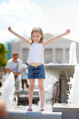 Preschooler girl playing with a city fountain