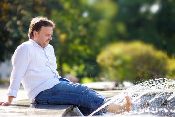 Man having fun in a city fountain