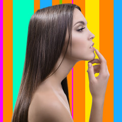 Beautiful young woman with long hair on colorful background