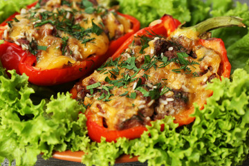 Stuffed red peppers with greens on on lettuce close up