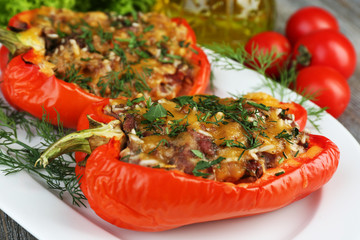 Stuffed red peppers with greens and vegetables on table close