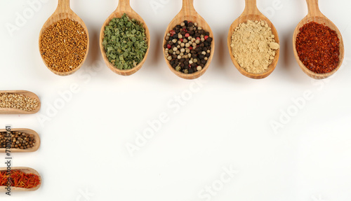 In de dag Kruiden 2 Different spices and herbs in wooden spoons isolated on white