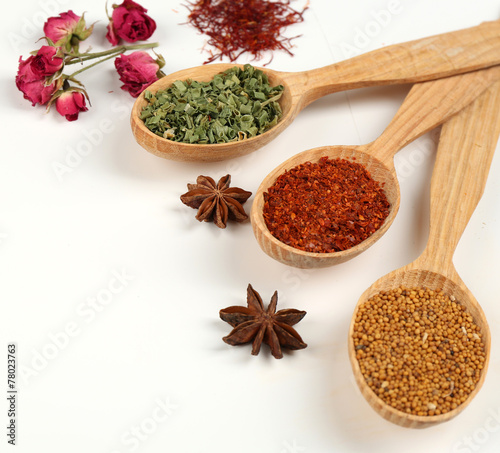 Fotobehang Kruiden Different spices and herbs in wooden spoons isolated on white