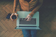 Laptop and coffee cup in girl's hands sitting on a wooden floor - 78024154