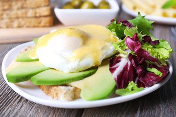 Toast with egg Benedict and avocado on plate on wooden table