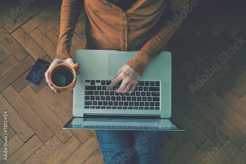 Leinwanddruck Bild Laptop and coffee cup in girl's hands sitting on a wooden floor