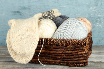 Knitting yarn and socks in basket, on wooden background