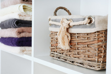 Colorful towels with wicker basket on shelf of rack background