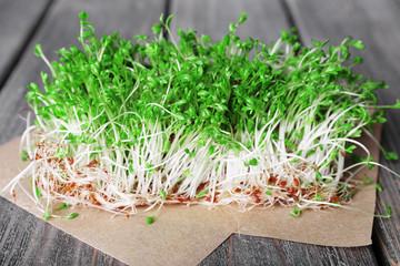 Fresh cress salad on wooden planks background