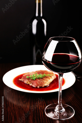 canvas print picture Glass of wine with grilled steak in wine sauce