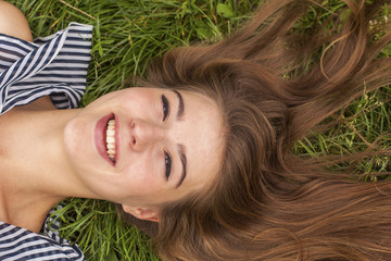 Fashionable girl lying on the grass, with scattered hairs.