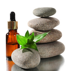 Spa stones with aromatic oils and green leaves isolated on