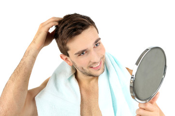 Handsome young man with towel holding mirror isolated on white