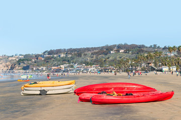 Group of red, white, yellow kayaks stacked on a busy beach