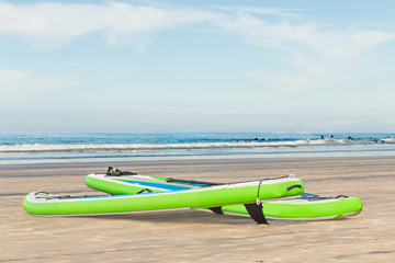 Pair of bright green stand up paddleboards on sandy beach