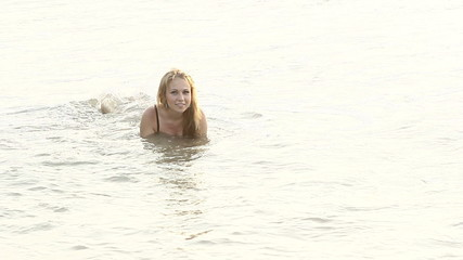 young blonde girl in black swimsuit lies in shallow seawater