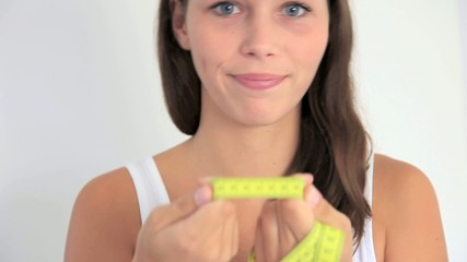 Young woman holding measuring tape