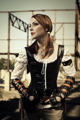 Attractive young l woman in leather corset posing outdoors.