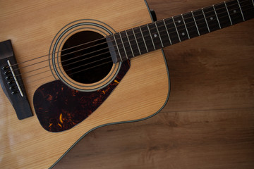 Close up shot of acoustic guitar on wooden table