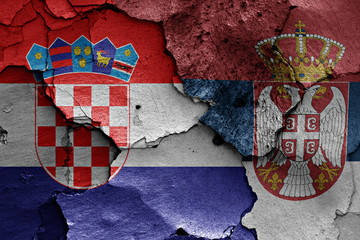 flags of Croatia and Serbia painted on cracked wall