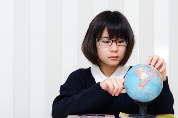 Teenage schoolgirl pointing a place on a globe with her finger