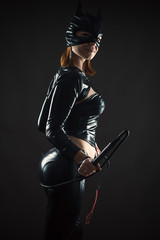 cat woman with a whip isolated on black background