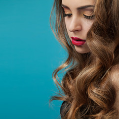 Woman with long hair on a blue background. Close up