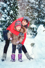 Happy mother and kid playing on snow