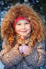 Little girl with candy in winter