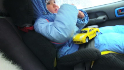Little boy sitting in baby car seat