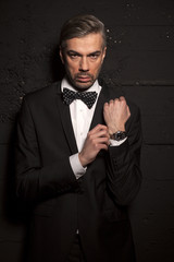 handsome man in a suit and bow tie on a black wall