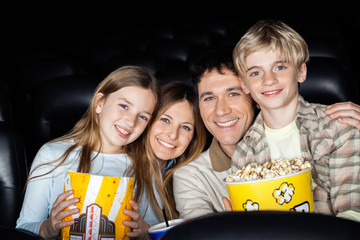 Happy Family With Popcorn At Cinema Theater