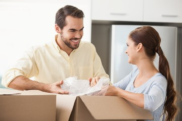 Young couple unpacking boxes in kitchen