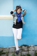 Beautiful positive woman posing in front of the blue wall