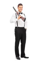 Elegant guy holding a shotgun over his shoulder
